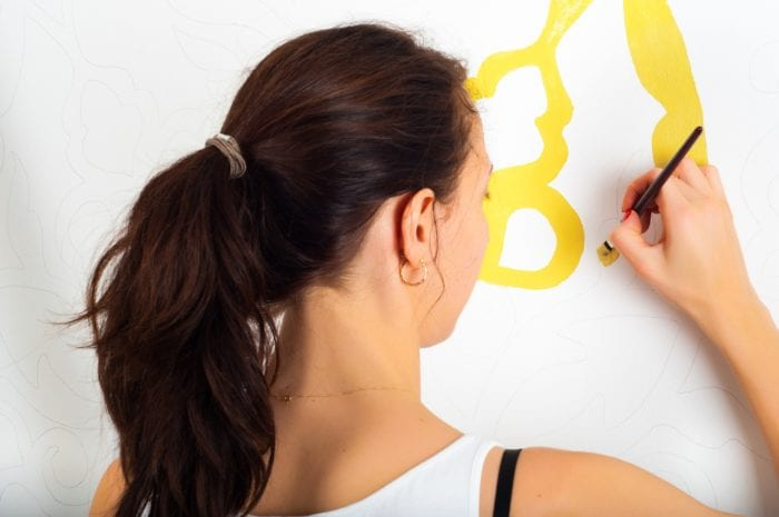 a woman with her back towards a wall painting a DIY with a small paintbrush