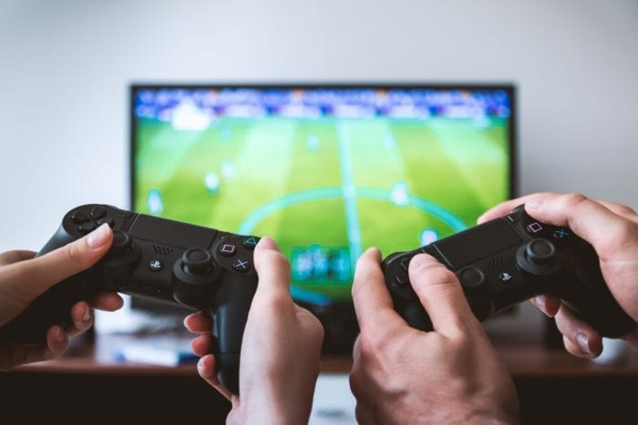 Two sets of hands holding controllers playing a video game on the TV