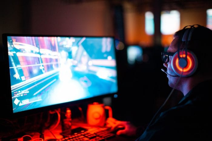Man wearing a headset with microphone playing an accessible video game on a computer