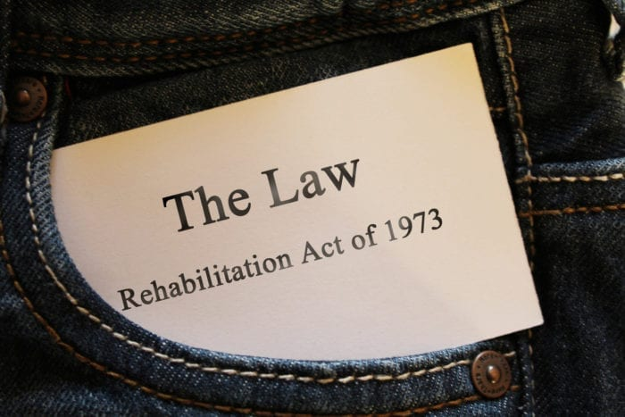 """Jean pocket with a card sticking out that says, """"The Law Rehabilitation Act of 1973"""""""