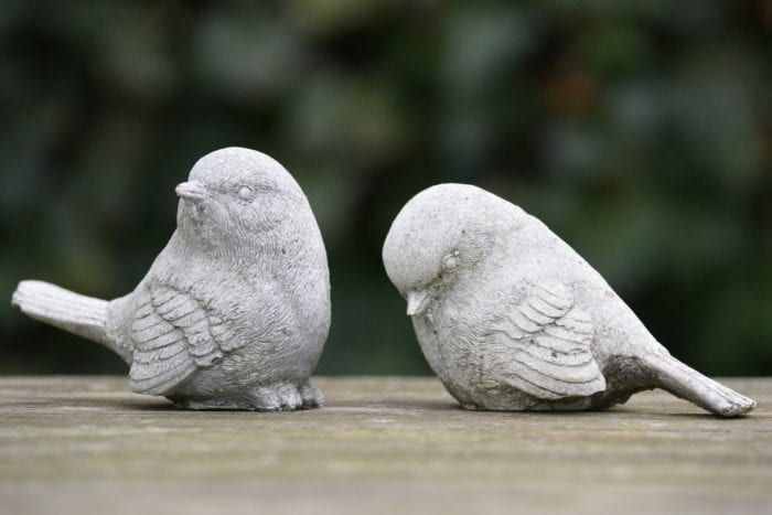 Exclusion of one stone bird that's looking down by another stone bird that's looking away