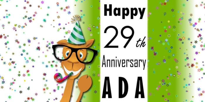 """Confetti background with Seymour wearing a party hat, blowing a noise maker, and pointing to the words, """"Happy 29th Anniversary ADA"""""""