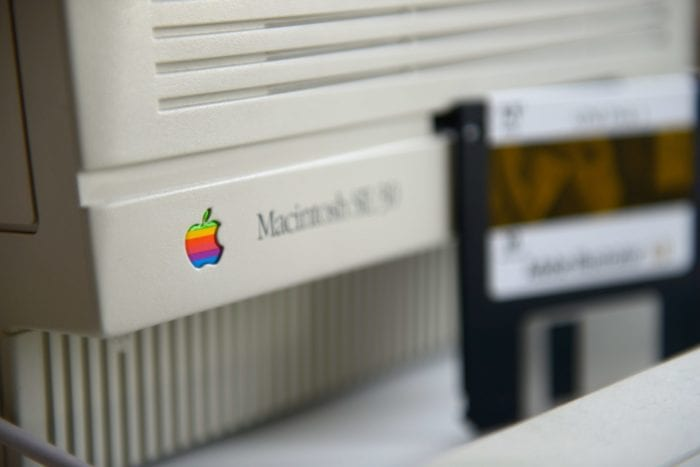 Close-up of the bottom right corner of a vintage Macintosh monitor and blurred out floppy disk