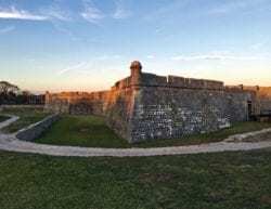 setting sunlight reflecting on an old fort with a clear blue sky and green grass