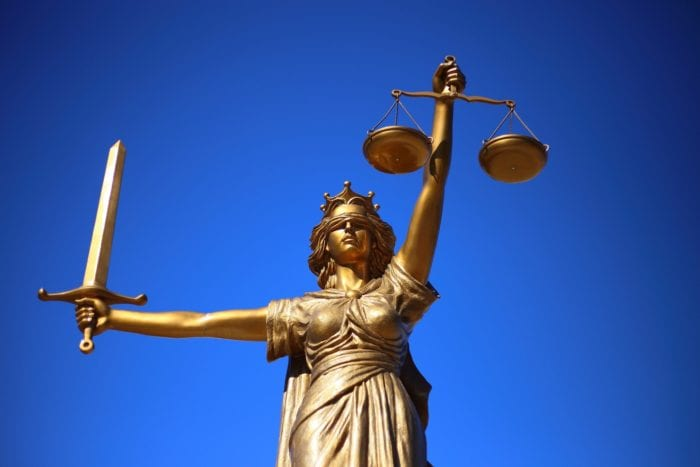 Statue of lady justice holding up her scales and sword