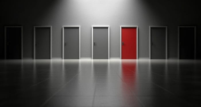 7 closed doors in an empty room with 1 door a different color than the rest