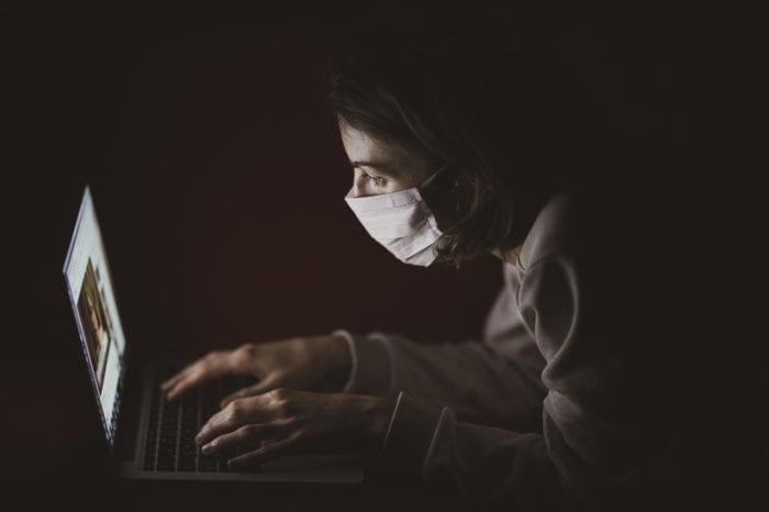 Someone with a mask close up to their computer screen reading COVID 19 communication.