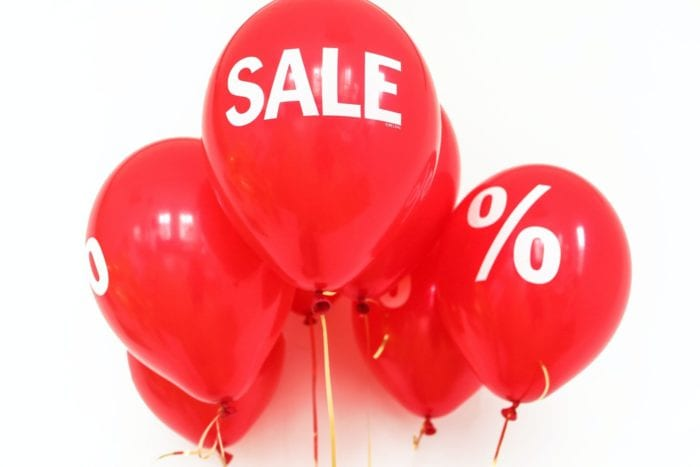 "Cluster of balloons with the word ""sale"" or a percent sign printed on them"
