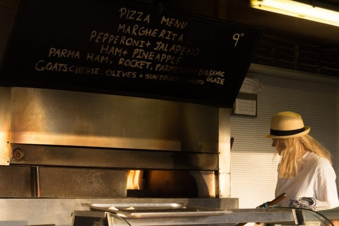 an employee at a pizza oven with the menu overhead written in chalk paint.
