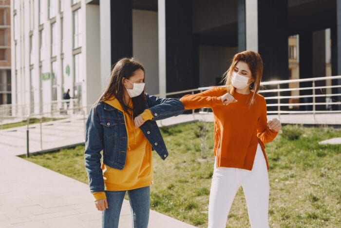 Two women outside wearing medical face masks and bumping elbows