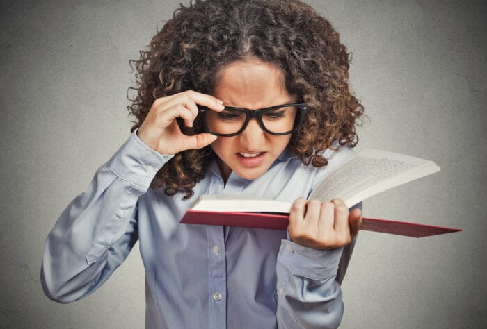 Woman with glasses struggling to read the print in a book