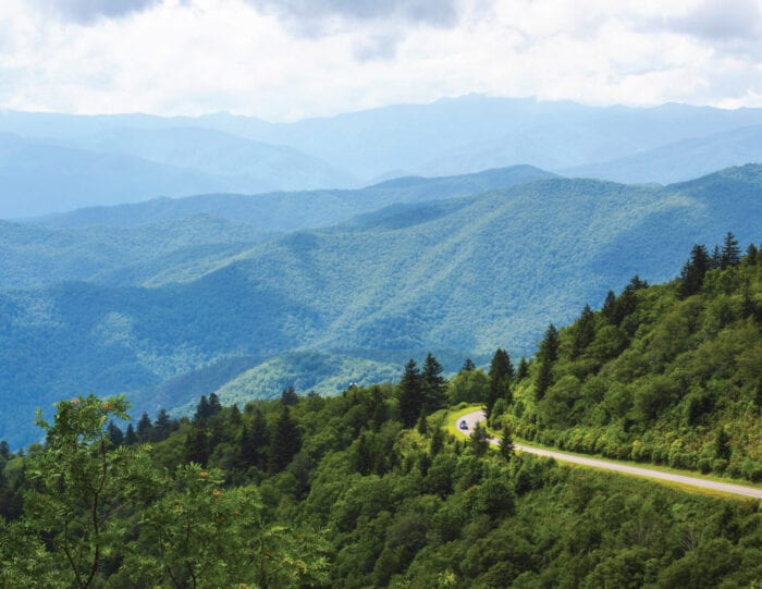 Smokey mountains covered with green trees and a lone road with one car