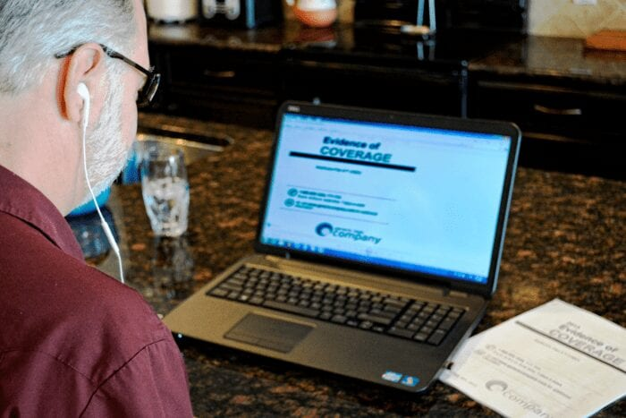 A man sitting in front of his laptop computer listening to a 508 Compliant accessible PDF document with Screen Reading software.