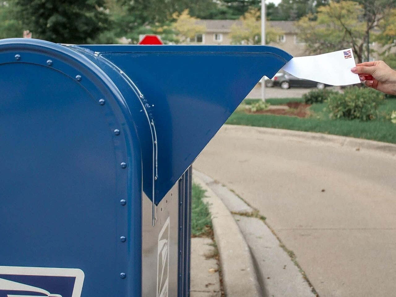 An American voter putting their accessible ballots in a mailbox.