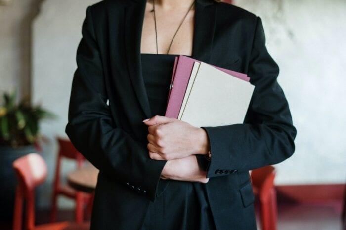 a hostess holding disposable menus