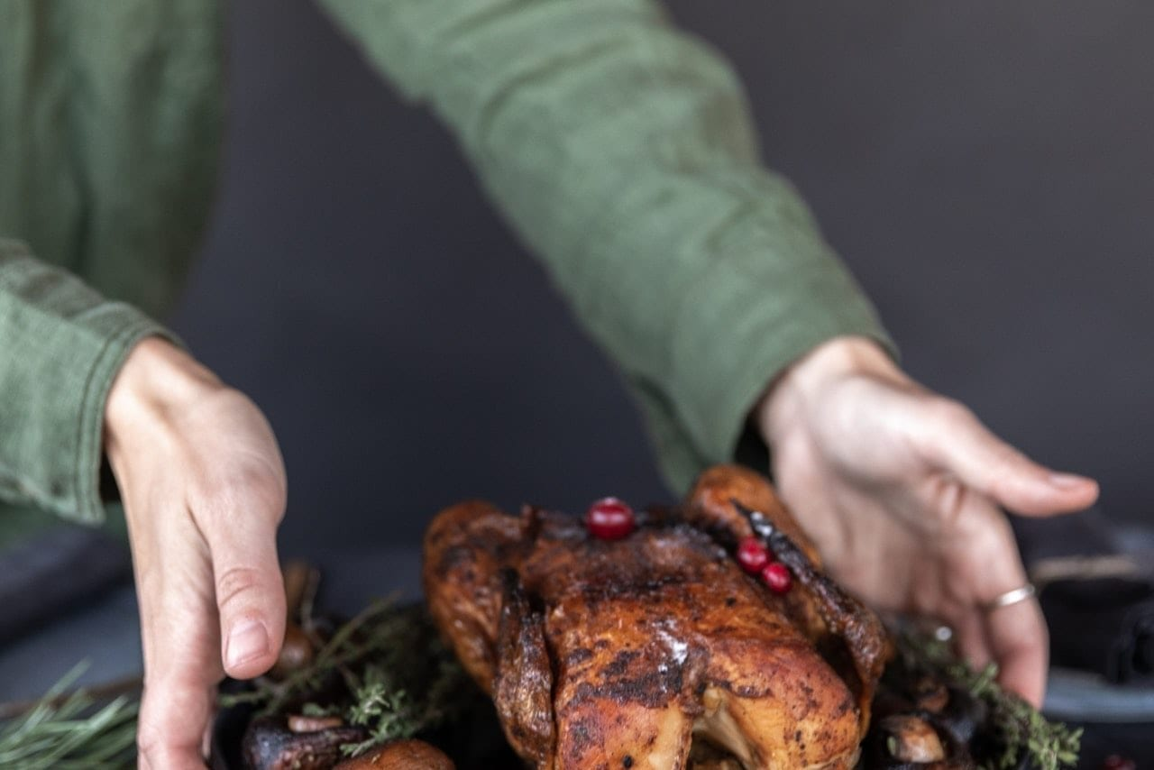 two hands setting a warm turkey on a table