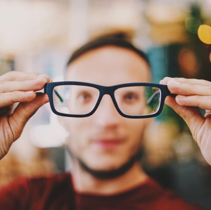 Blurry image of a man holding up in-focus glasses