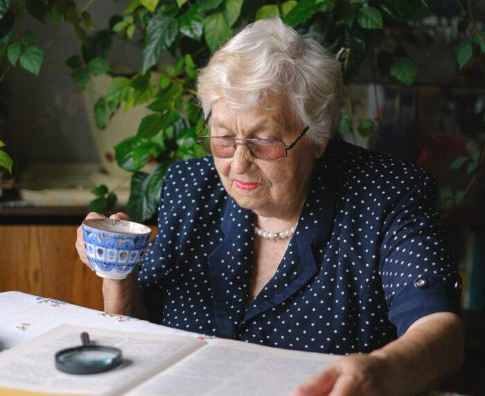Senior citizen woman reading a book while drinking tea