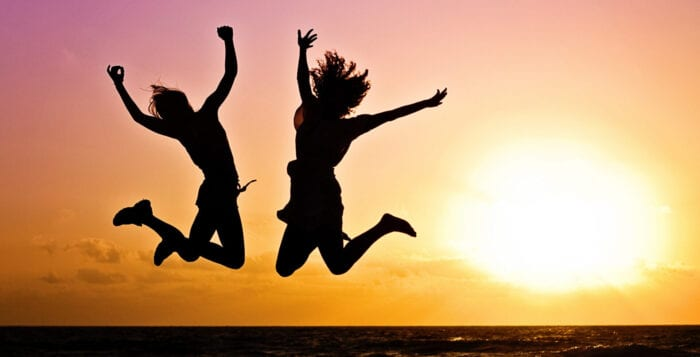2 women jumping in celebration in front of sunset
