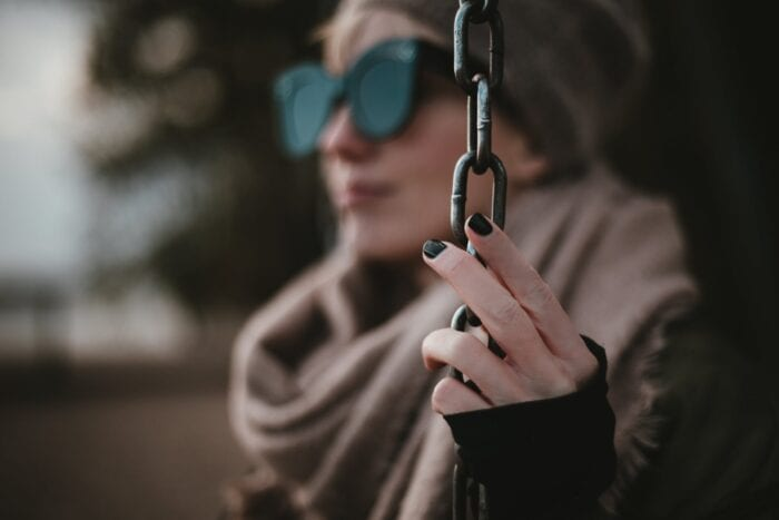 Woman wearing sunglasses holding onto a vertical chain