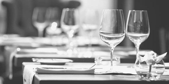 Image of stemware, plates, and silverware set nicely on a restaurant table