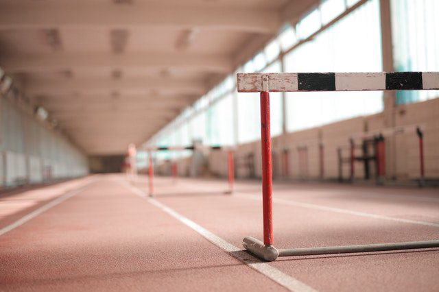Row of striped hurdles in a gymnasium with soft lighting.